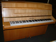 Bentley modern upright piano in a light oak cabinet.