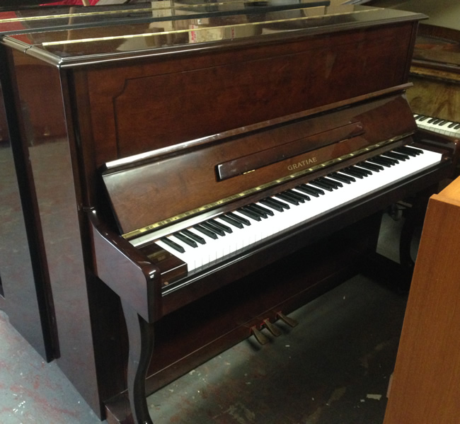 Gratiae upright piano in a Mahogany high gloss finish.