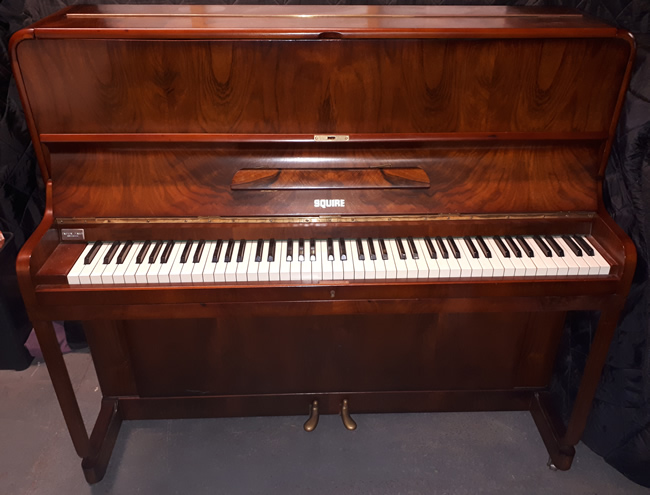 Squire upright piano in a Walnut satin cabinet.