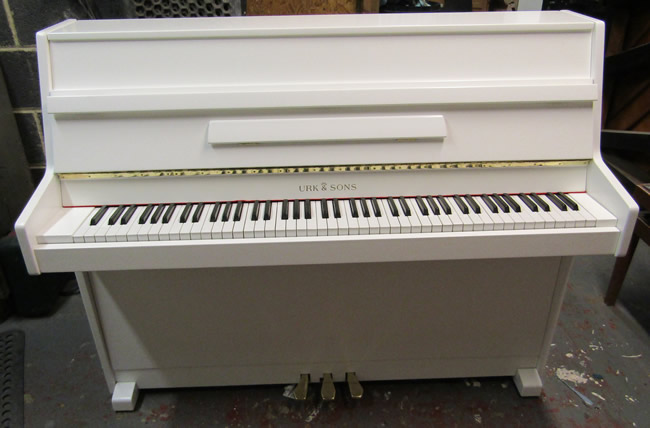 Urk & Sons white satin modern upright piano.